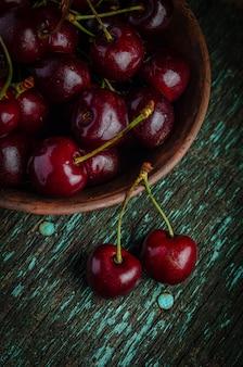 木製の古いテーブルに熟した赤いチェリーと粘土板。