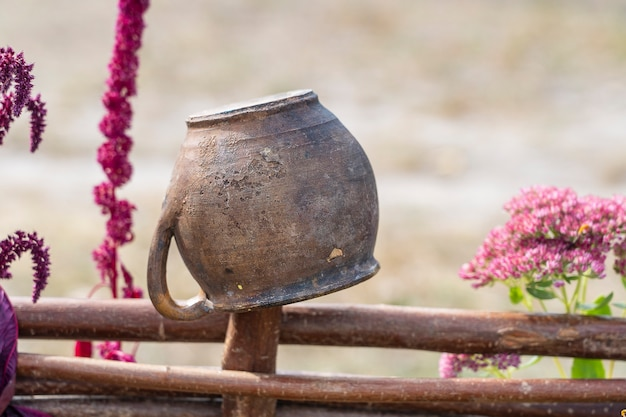 Clay pot and flowers on wicker fence, outdoors, ukraine. rural ukrainian national style