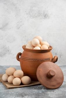 대리석에 원시 닭고기 달걀이 가득한 항아리.
