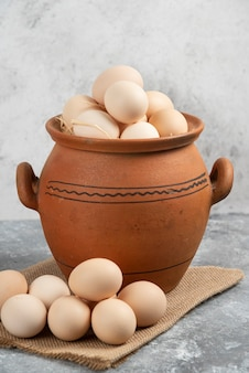 Clay pot full of raw chicken eggs on marble.