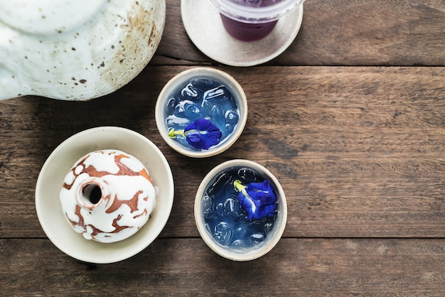 Clay pot of  iced butterfly pea tea on wooden table