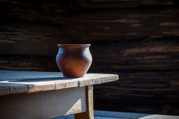 Clay pot on an old wooden table in an old rustic house. pottery and peasant life. still life with pottery