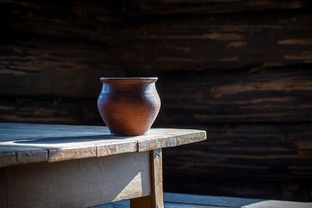 Глиняный горшок на старый деревянный стол в старом деревенском доме. гончарная и крестьянская жизнь. натюрморт с глиняной посудой