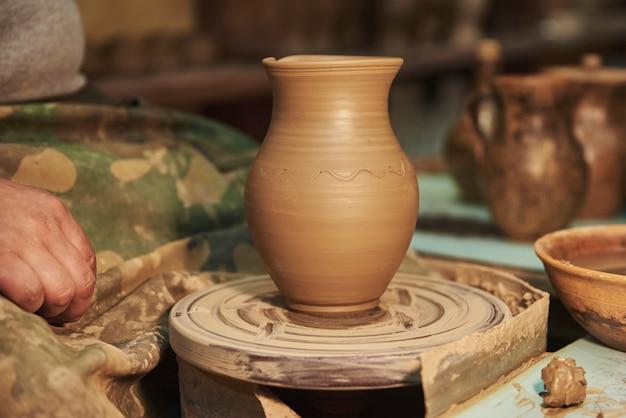 Глиняный горшок на гончарном круге в интерьере мастерской