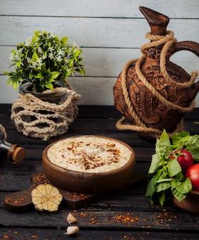 Глиняный горшок с мясом, покрытым плавленым сыром