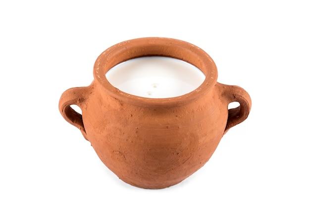 Глиняный горшок с молоком на белом фоне