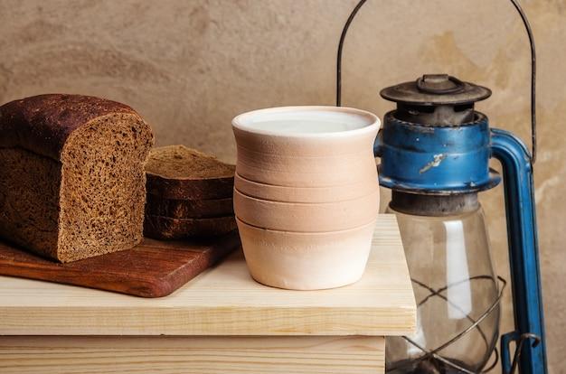 Глиняный горшок с молоком, ржаным хлебом и керосиновым фонарем. натюрморт в деревенском стиле