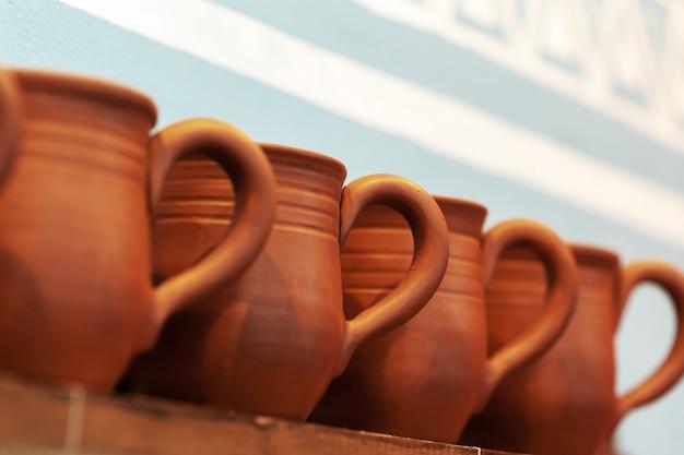 Глиняные горшки на деревянной полке крупным планом Premium Фотографии