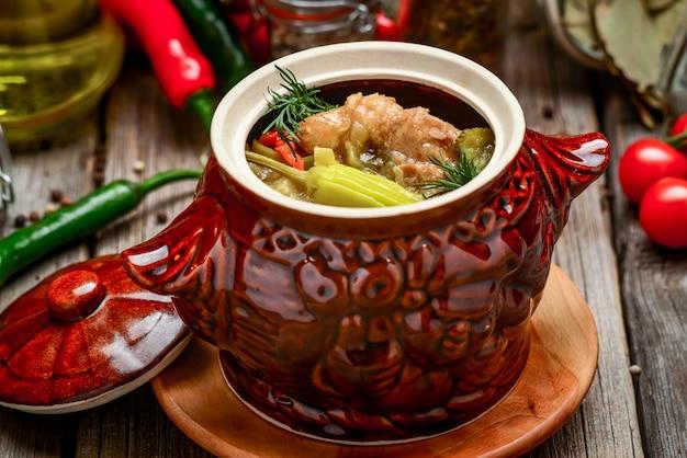 Глиняные горшочки с запеченным картофелем и куриным мясом с тыквой и рубленой зеленью на деревянной доске