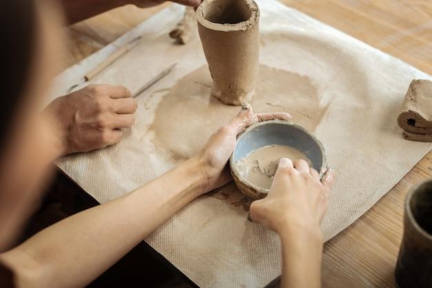 粘土物質。手で花瓶を形成するための粘土物質を作るプロの創造的な陶芸家のカップル