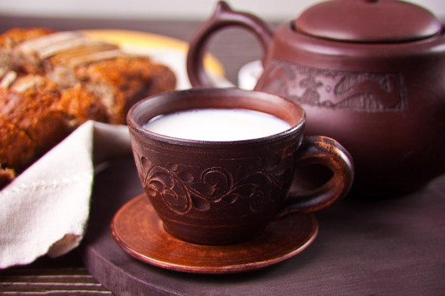 Clay tea cup with teapot on old wooden table
