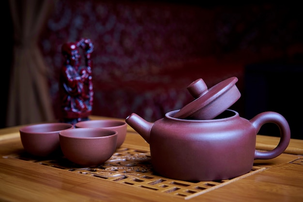Clay tea set stands on a wooden board.