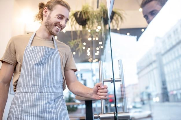 깨끗하고 안전합니다. 결과에 만족하는 손잡이를 들고 유리 문 근처 카페에 서있는 앞치마에 즐거운 젊은 수염 난된 남자