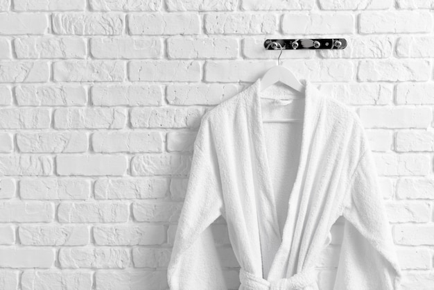 Clean bathrobe hanging on brick wall