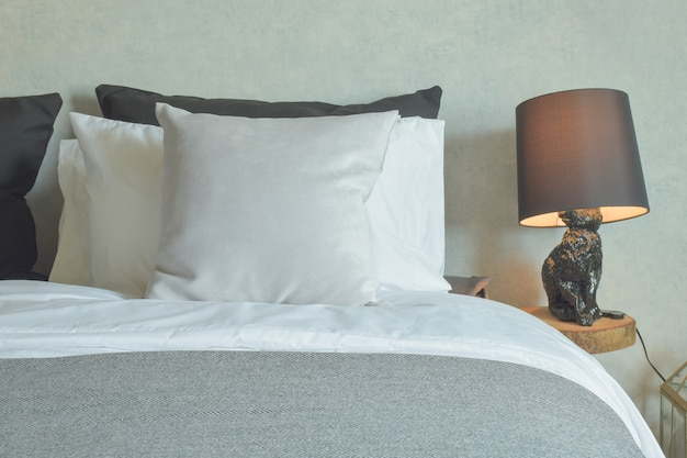 Clean bed in hotel guestroom with brown reading lamp