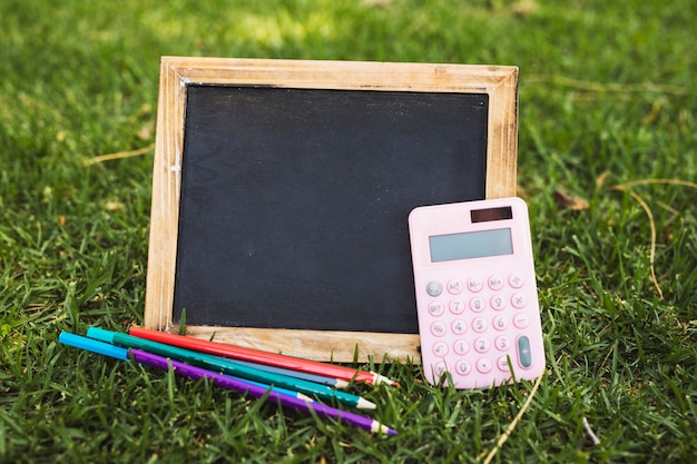 Clean blackboard with pencils and calculator on grass