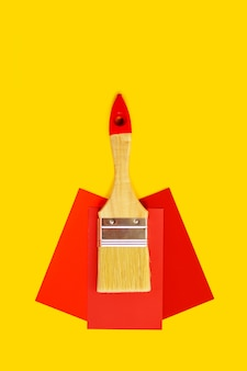 Clean brush and paint color choice template on yellow background with copy space.