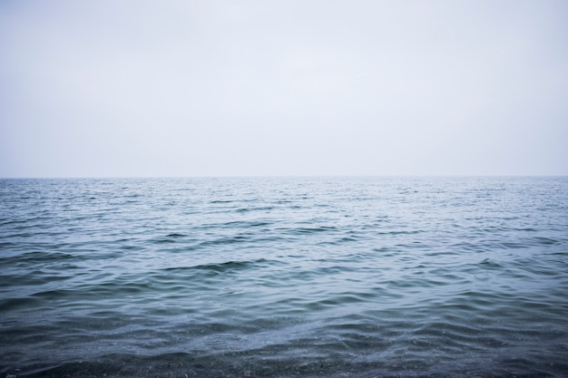 Clean and calm blue sea or ocean. mist above the water surface