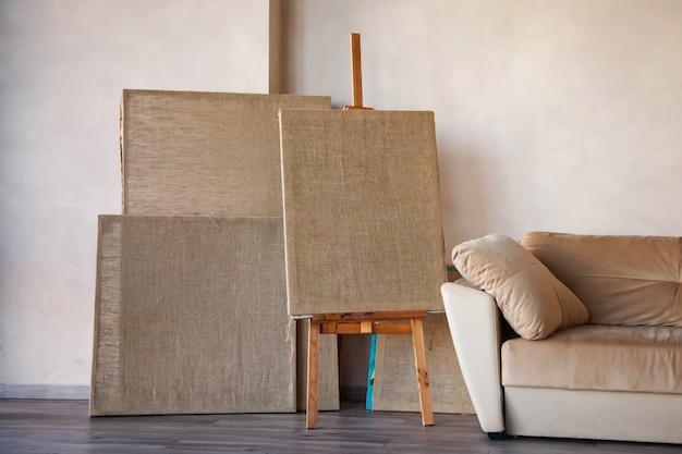 ソファのそばの部屋の明るいインテリアにあるアーティストのためのきれいなキャンバス。帆布と帆布は絵画用のスタンドです。アートワークショップの背景。アーティストの家。驚くべき、現代的な、抽象的な。コピースペース