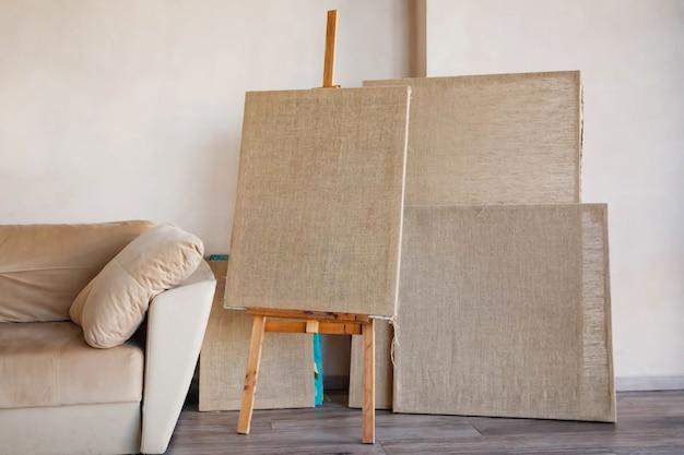 ソファのそばの部屋の明るいインテリアでアーティストのためのきれいなキャンバス