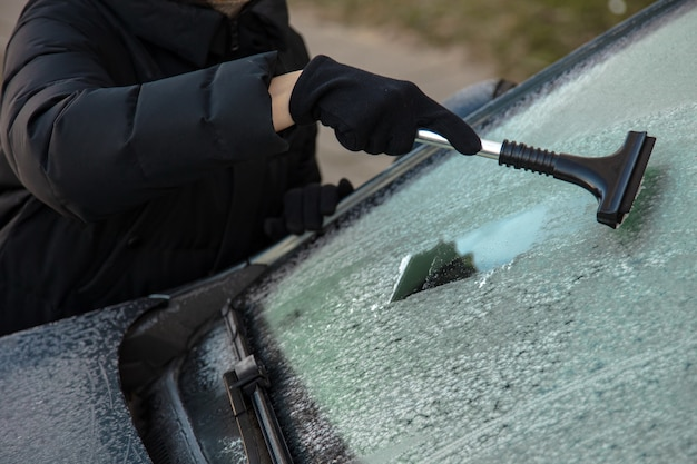 Зимой очищайте окна машины от снега. мойка лобового стекла автомобилей. удаление льда и снега с окон.