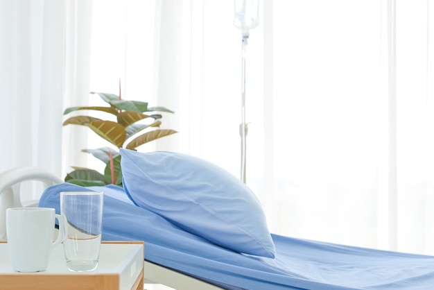 Clean and clear empty hospital near sunny window, blue bed linen with white curtain in ward room for background