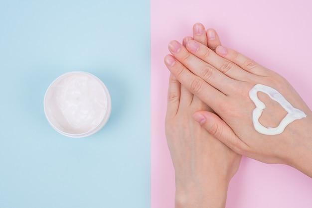 Концепция натурального питательного ухода за ногтями clean clear finger. над верхними накладными высокими углами плоской планировки крупным планом вид на красивые безупречные ароматические руки, изолированные сине-розовой пастельной поверхностью