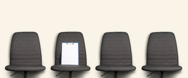 Clean clipboard lies on a gray office chair against a light background. banner.