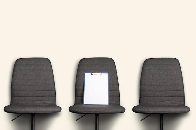 Clean clipboard lies on a gray office chair