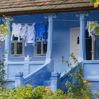 青い農家の中庭できれいな服を乾かす
