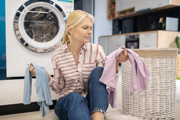 Чистая одежда. блондинка домохозяйка в полосатой рубашке сидит возле стиральной машины и держит одежду