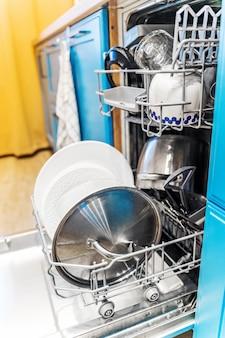 밝은 파란색 목재로 주방의 개방형 식기 세척기로 식기를 청소하십시오.