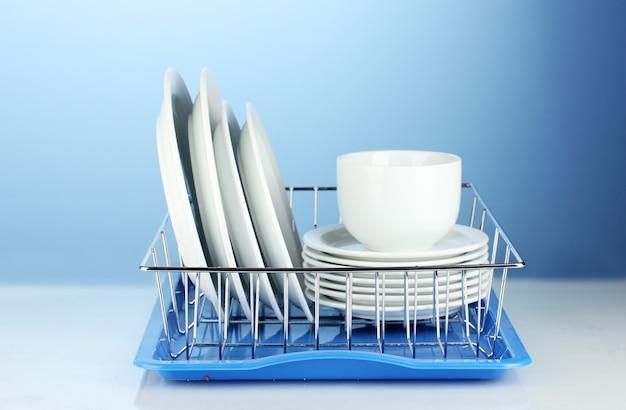 Чистая посуда на подставке на синем