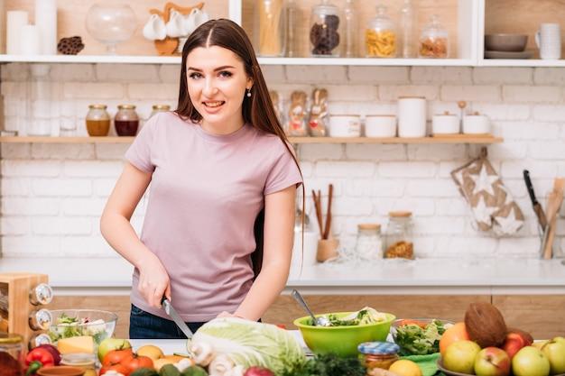 깨끗한 식사. 유기농 레시피. 건강한 전체 식품 영양. 저녁 식사를 요리하는 부엌 카운터에서 젊은 여성.