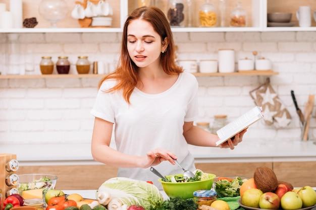깨끗한 식사. 유기농 레시피. 건강한 전체 식품 영양. 저녁 식사를 요리하는 손에 책을 가진 젊은 여성.