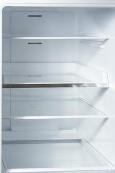 Очистите пустые полки в белом холодильнике.