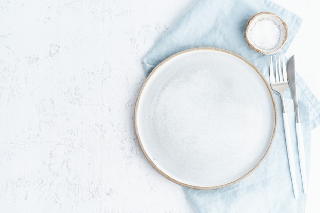 Clean empty white ceramic plate, fork and knife on white stone table, copy space, mock up