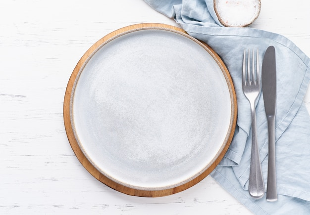 Clean empty white ceramic plate on white stone table, copy space, mock up, top view.