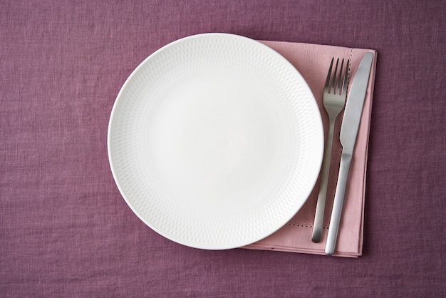 깨끗한 빈 흰색 접시, 포크와 나이프 테이블에 밝은 블루 베리 레드 린넨 식탁보, 모형