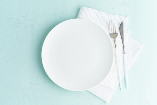 Clean empty white plate, fork and knife on green blue turquoise stone table, copy space