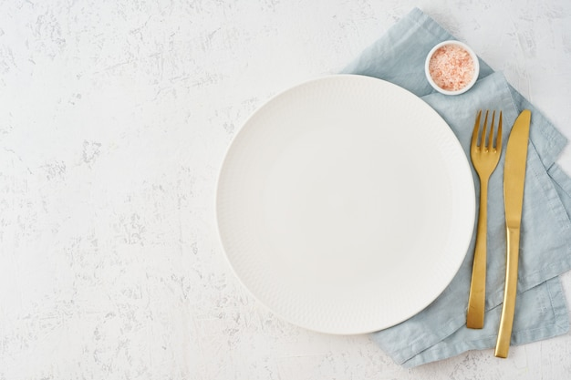 Clean empty white plate, fork and knife on white stone table, copy space, mock up