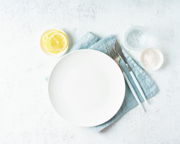 Clean empty white plate, glass of water, fork and knife on white stone table, copy space, mock up
