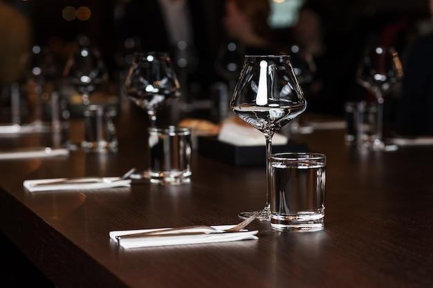 Чистые стаканы и столовые приборы на столе в ресторане
