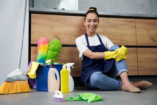 きれいな家。洗剤で床掃除をした後、休憩中にカメラに向かって笑っている幸せな若い女性の全身ショット。家事とハウスキーピング、クリーニングサービスのコンセプト
