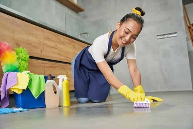 クリーンアップします。自宅で洗剤で床を掃除しながら笑っているうれしそうな若い女性のフルレングスのショット。家事とハウスキーピング、クリーニングサービスのコンセプト。ローアングルビュー