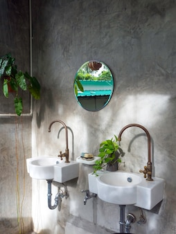 두 개의 흰색 현대 싱크대, 황동 수도꼭지, 냄비의 녹색 잎 및 콘크리트 벽에 둥근 거울이있는 깨끗한 로프트 스타일의 욕실 인테리어