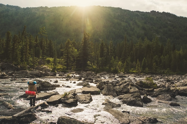 Clean mountain creek with blue pure water flowing on colorful watercourse and hiker in sporty shoes crossing the river jumping on stones trendy toned sunlight