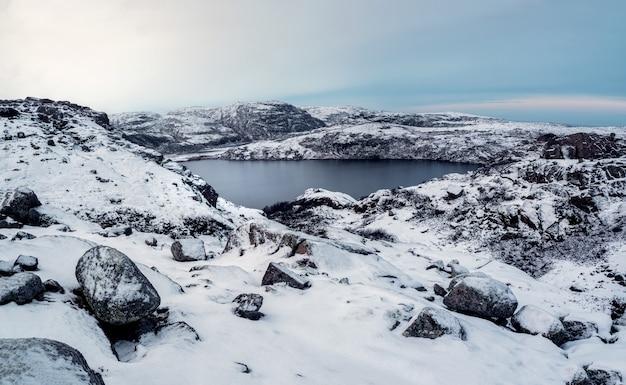깨끗한 산 호수, 탁 트인 겨울 전망. 높은 고도의 얼어 붙은 호수가있는 놀라운 북극 풍경.
