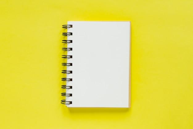 目標と解決のためのきれいなメモ帳。あなたのデザインのモックアップ。黄色の背景にスパイラルメモ帳。
