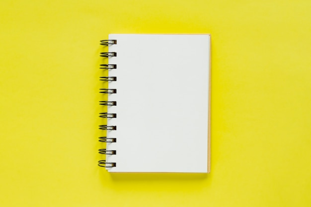 Clean note book for goals and resolutions. mockup for your design. spiral note book on yellow background.